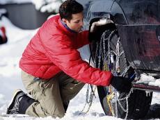 Hombre colocando cadenas de nieve